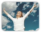Joyful, smiling woman with outstretched arms with blue skies behind her