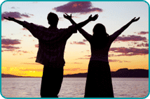 A silhouette of a couple with their arms outstretched overlooking the ocean at sunset