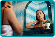 Woman looking at herself in bathroom mirror