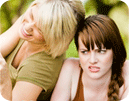 Woman sneering at her laughing friend