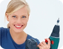Smiling blonde woman holding power drill