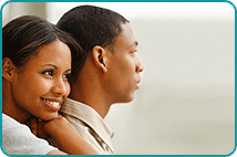 Smiling woman holding man from behind as he looks coldly into the distance
