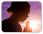 Silhouette of praying woman at sunset