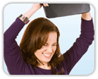 Frustrated woman holding bathroom scale over her head