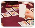 A tarot card spread with the tarot reader holding a blank card
