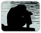 Silhouette of a depressed person considering their options on a pier overlooking a lake