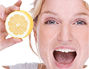 Happy, smiling woman holding up half of a lemon