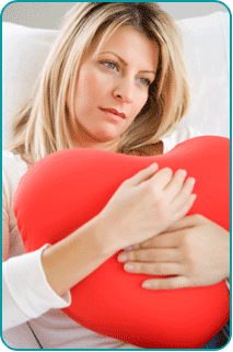Woman on couch hugging heart-shaped pillow