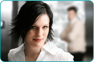 Smiling woman thinking about how to get her ex-boyfriend back, as he stands, blurred, in the background