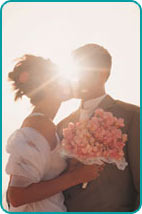 A couple kissing on their wedding day with the sun peeking through, between their faces
