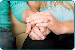 Close-up of the hands of a woman holding the hand of another, consoling them