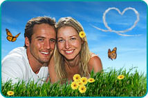 A smiling couple lying in the grass with yellow daisies and a heart formed in the sky by sky writing