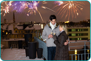 A couple on the roof of a city building as a New Year's Eve fireworks display occurs in the background