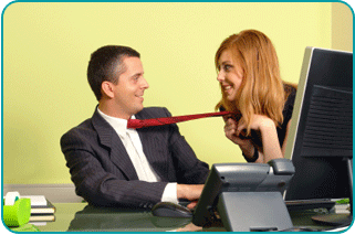 A woman flirtatiously holding a man's tie as he sits as his office desk