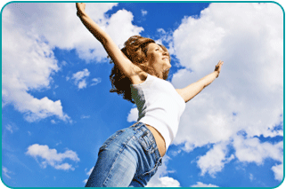 A happy woman stretching out her arms in triumph with a bright blue sky behind her