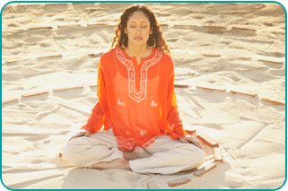 A woman meditating in the lotus position on the beach