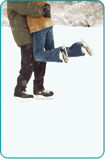 The lower half of a man holding his girlfriend up as they skate on a frozen pond