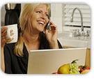 Smiling woman with coffee cup in hand, at her laptop as she talks to her psychic on the phone